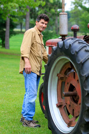next year: Handsome 50 year old Man next to a Vintage tractor Stock Photo