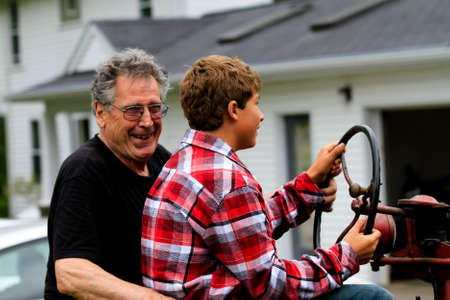 Grandfather teaching his Grandson how to drive a stick shift on a Tractor photo