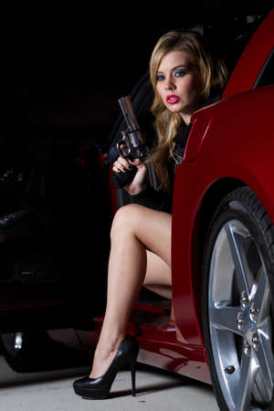 Beautiful Blonde Woman in her twenties holding a gun siting in a car. Shot at night with Strobes for shadowing effect. photo