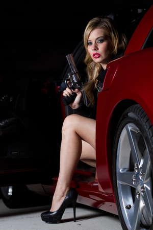 mujer policia: Hermosa rubia mujer en sus veinte a�os con una pistola emplazamiento en un coche. Filmada en la noche con luces estrobosc�picas para sombrear efecto. Foto de archivo