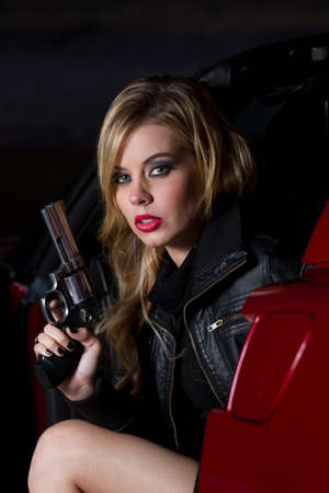 Beautiful Blonde Woman in her twenties holding a gun siting in a car. Shot at night with Strobes for shadowing effect.