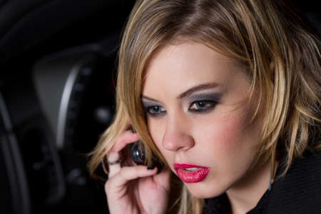 Beautiful Blond Woman talking on a Cell phone in a car at night photo