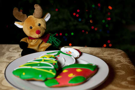 Christmas Cookies and a toy Raindeer in front of the Christmas tree with bokeh from the lights photo