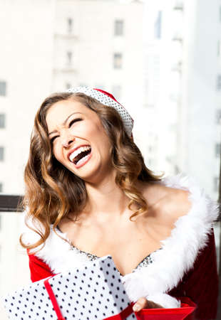 Beautiful Woman in a sexy santa outfit with a present photo