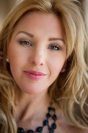 one mid adult woman: Closeup of a Pretty Blond Woman Smiling with Lips Closed