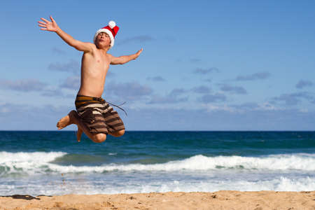 A Teen Boy Wearing a Santa Hat Jumping on the Beach in Hawaii Stock Photo