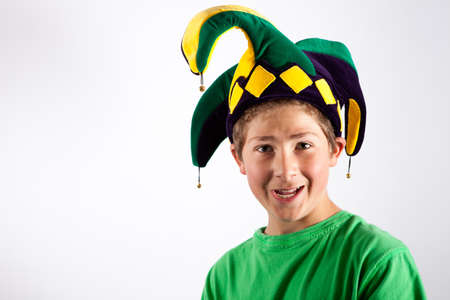 jester hat: Child in a green shirt wearing a Green, Blue & yellow Jester Hat Stock Photo