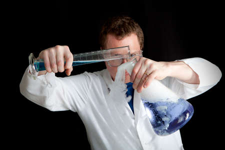 causing: Scientist Experimenting pouring a blue liquid from a tube into a large beaker causing a Gaseous Smokey reaction Stock Photo