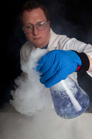 causing: Scientist Experimenting with a blue liquid in a large beaker causing a Gaseous reaction with smoke