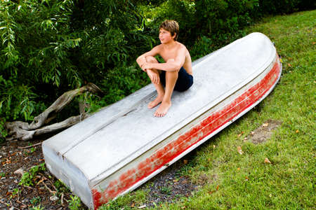only teenagers: In the country a Handsome Boy Teenager is on Sitting on a Boat Stock Photo