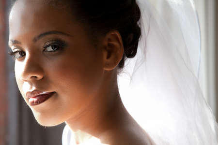bridal veil: Beautiful Bride looking out a window Stock Photo
