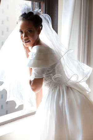 Beautiful Bride looking out a window photo