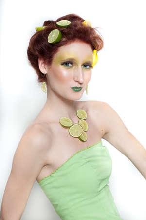 Beautiful woman in Lemon Lime creative makeup with real fruit photo
