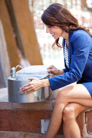 Pretty Smiling Businesswoman at a drinkin fountain Stock Photo - 13562273