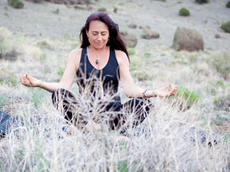 Pretty middle aged woman meditating in nature, Colorado photo