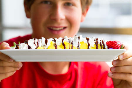 bannana: Teenager holding a sushi dessert made with Bannana, strawberries, chocolate and whip cream Stock Photo