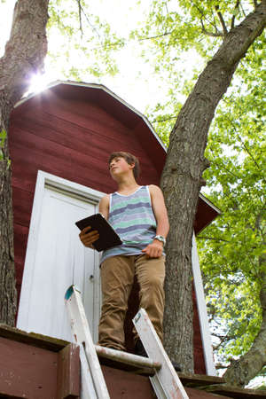 Teenager  reading a touchpad  infront of a Treehouse Stock Photo
