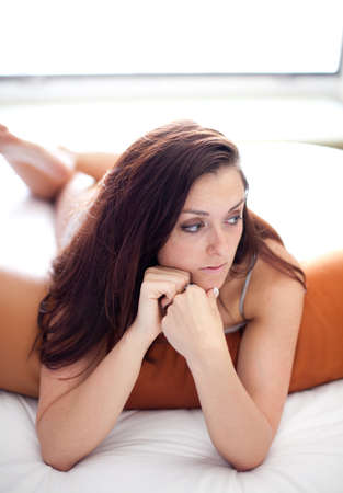 deep thought: Pretty Woman deep in thought lying down Stock Photo
