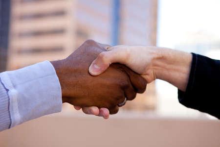 Handshake of Friendship between two races Stock Photo - 14121373