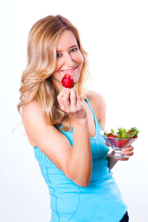 Pretty woman enjoying a bowl of strawberries photo