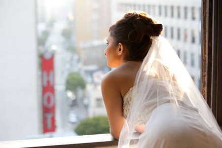 Beautiful Bride looking out a window in reflection of her romance photo