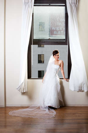 Beautiful Bride in a window with city behind her photo