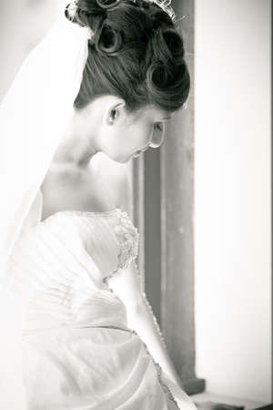 Beautiful Bride lin a window looking away from camera photo