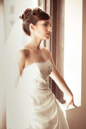 Beautiful Bride in a window with aged developing photo