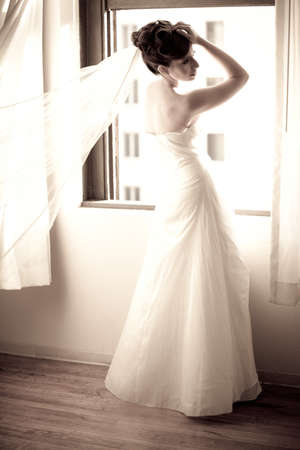 Beautiful Bride with veil blowing in the window photo