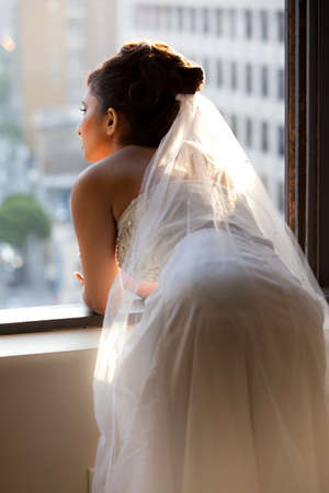 Beautiful Bride looking out a window in reflection of her new life photo