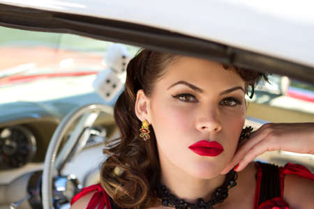 red dice: Beautiful Brunette woman looking out of a car window with dice hanging in the windshield