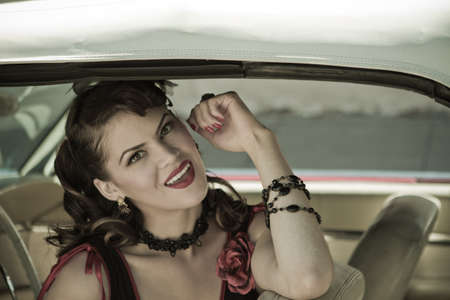 Beautiful Brunette woman looking out of a vintage car photo