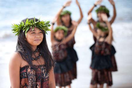 Hula girl on the beach with her fellow dancers behind her 版權商用圖片