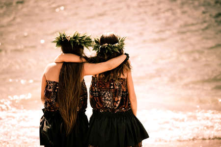 youth culture: Two teenage Hula girls walking into the ocean Stock Photo