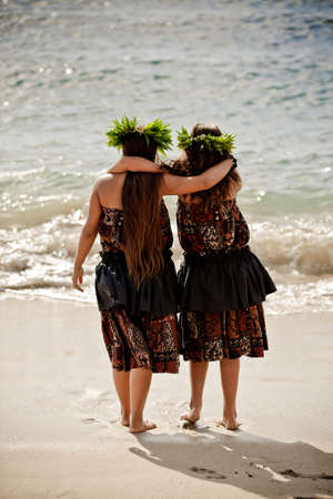 Two teenage Hula girls walking into the ocean photo