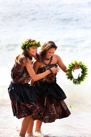 Hula girls on the beach laughing and playing in the water Stock Photo - 14285512