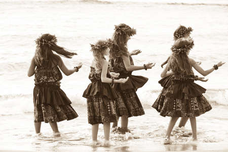 Hula girls on the beach in Sepia textured grain photo for aging effect photo