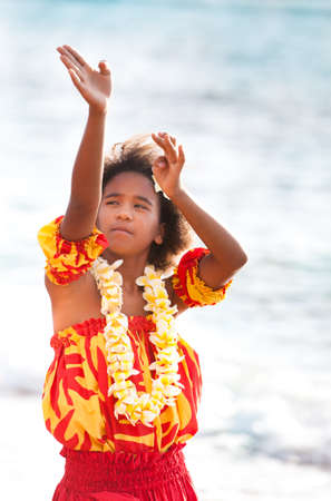 Pretty Hula Girl dancing at the beach in traditional dress at the beach wearing a handmade flower lei photo