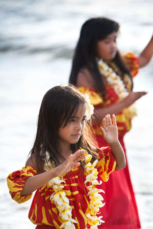 Pretty Hula Girl dancing at the beach in traditional dress photo