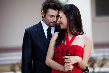 Beautiful Asiian Woman with Red Roses in a Red Dress with her Lover looking at her photo