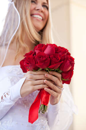 A Bride holding a Beautiful Red Rose Bouquet photo