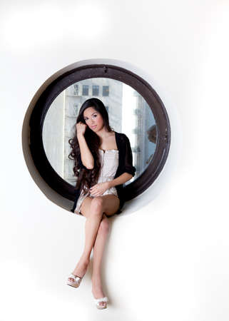 Pretty Hispanic Woman wth Beautiful Long Hair sitting in the quiet space of a circle window photo