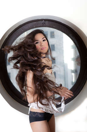 Pretty Sexy  Hispanic Woman wth Beautiful Long Hair sitting in the a circle window with city buildings in the background Stock Photo - 14285476
