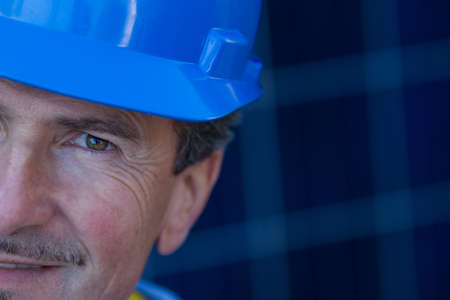 Close up of a Man in his forties overseeing a Solar Instalation focus on his eye on you to think of energy photo