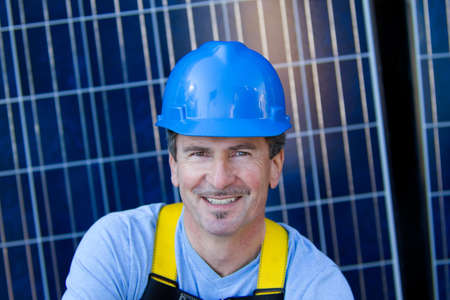 Close up of a Man in his forties overseeing a Solar Instalation with Solar Panels behind him photo