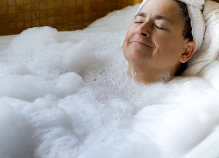 Closeup of middle aged lady  the bathtub Relaxing with bubbles photo