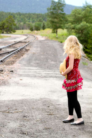 Pretty Blonde Girl by the train tracks thinking of traveling  photo