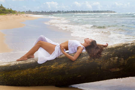 Beautiful Woman Lying on driftwood in Kauai photo
