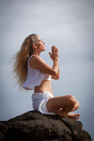 middle age women: Pretty Happy Middle Aged Woman with long hair Meditating in Hawaii on a Lava bed