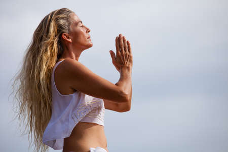 Beautiful woman with long hair in her Forties Meditating in Hawaii on a Lava bed photo